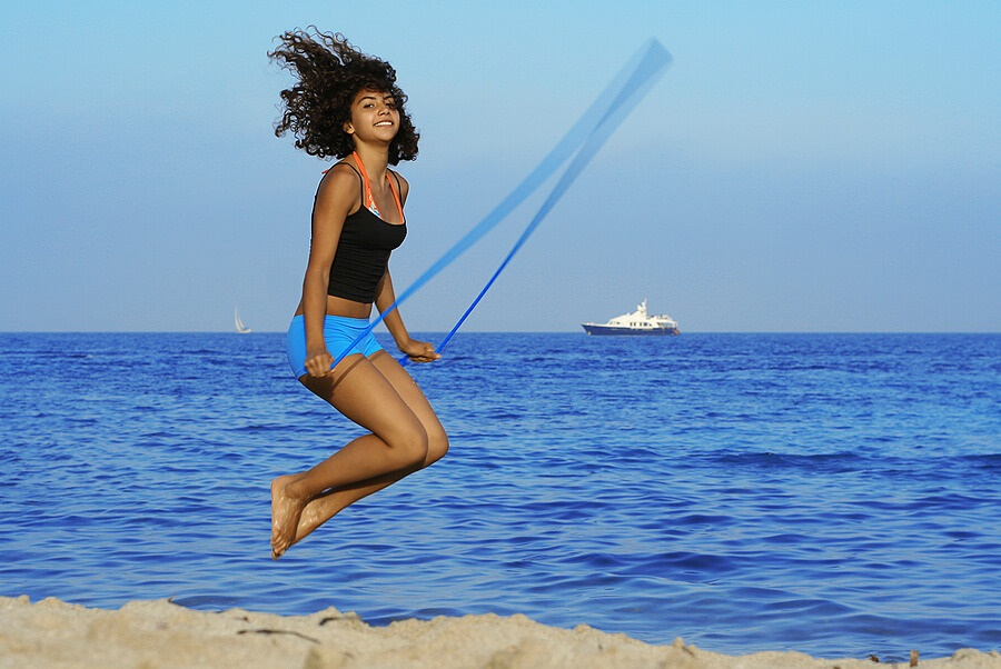 Fun Family Fitness, Teen girl jump roping on beach for exercise