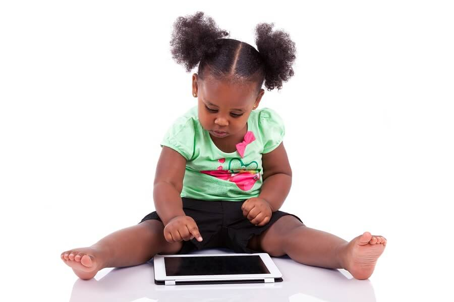 Little girl with pigtails using tablet against white background