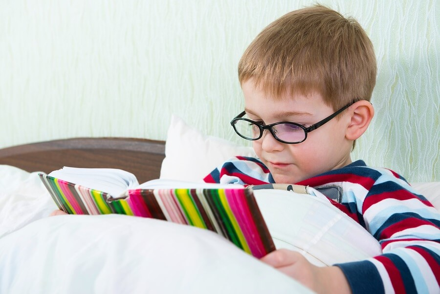 Little boy relaxing in bed reading.