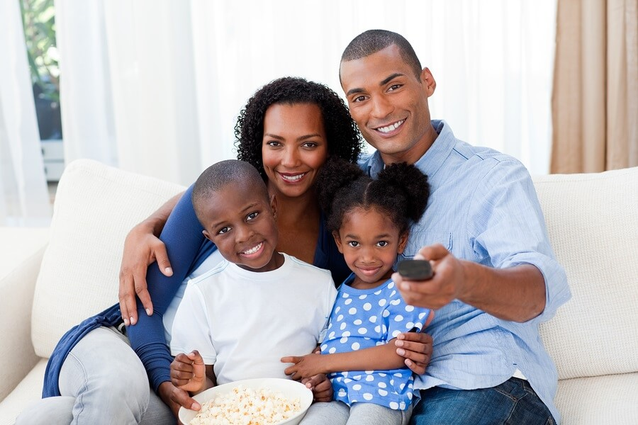 Happy family sitting on couch watching movie